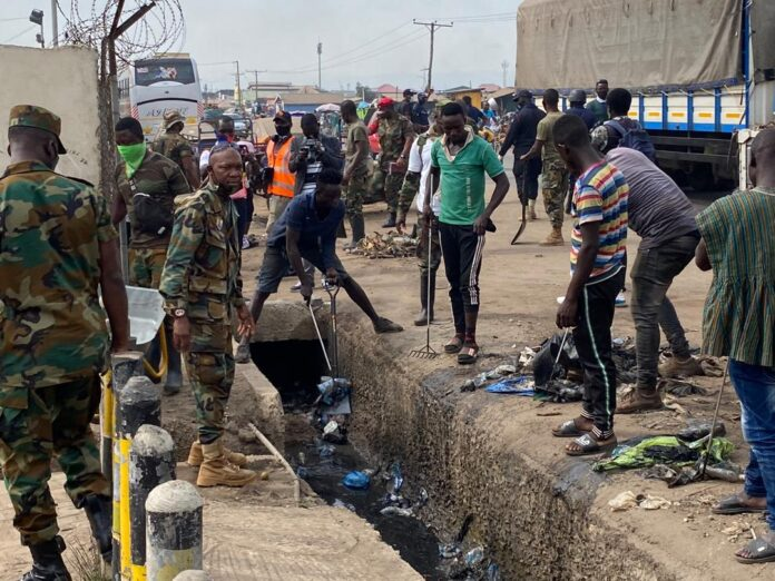 Photo of Military Men Force Persons Without Nose Masks To Clean Gutters